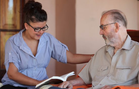 companion or granchild reading to elderly senior or grandfather